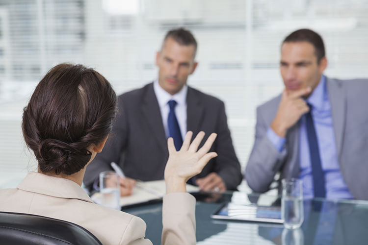 Brown haired woman talking to her interviewers in bright office
